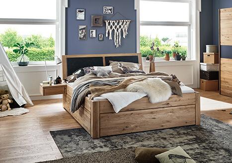 Bett in Komforthöhe und mit Schubläden und Nachttisch in Wildeiche