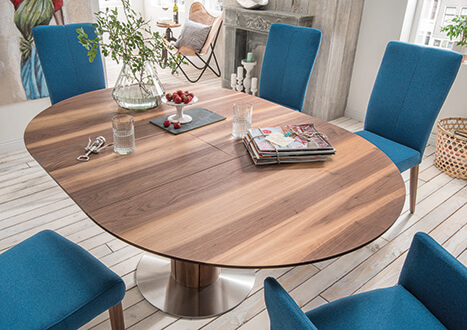 Ovaler Esstisch mit Ausziehfunktion aus massivem Nussbaumholz mit blauen Polstersesseln